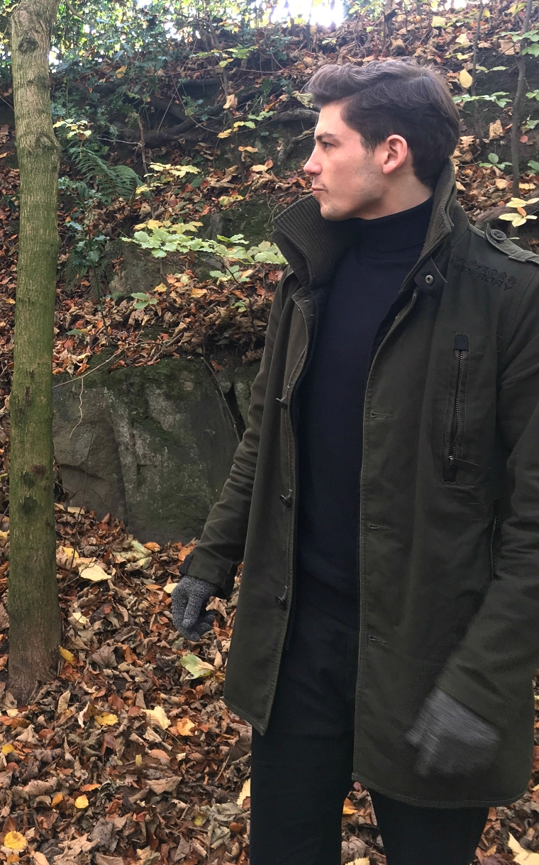 man wearing green superdry coat in woods