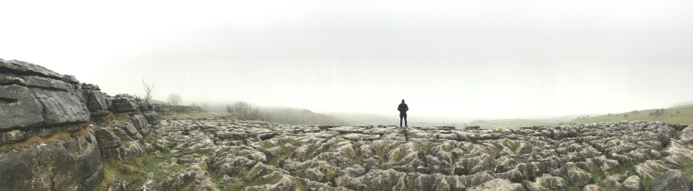 mans silhouette on rocks overlooking the countryside